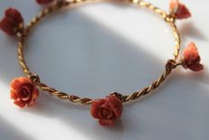 Yellow gold bracelet inlaid with coral roses.