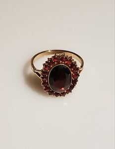 Gold ring with oval facet cut garnet with 18 small garnets