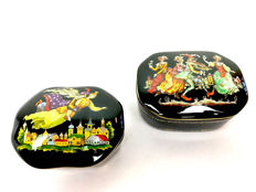 Two porcelain music boxes in the form of a lacquer box with Russian/Italian figures: Pulcinella en Ruslan and Ludmilla
