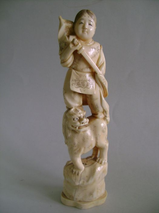Ivory Okimono. Young warrior on a guardian lion. Signed Masakazu - Japan - Ca. 1900 (Meiji era)