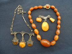 Vintage brooch with silver rooster and two necklaces, one with amber beads, one with silver coloured chainlet and three amber  pendants