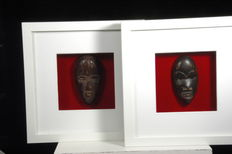 Two African miniature masks in framework