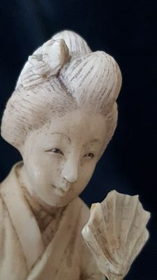 Okimono made of ivory of a lady with a flower and a fan - Japan - 1900