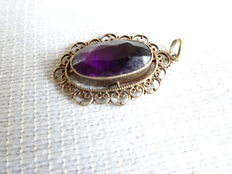 Beautiful gold pendant with purple-coloured stone
