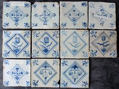 Eleven antique Dutch tiles - all with tulips in jagged square with lily corners