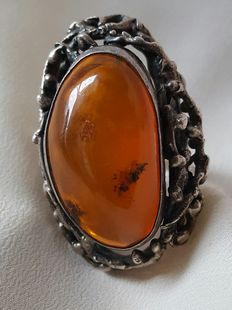 Old large silver ring with cabochon cut Baltic amber.