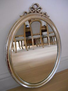 ornate mirror in silver-plated wooden frame