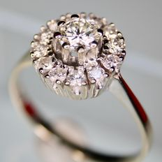 Beautiful ring with a natural brilliant cut solitaire diamond of approx. 0.40 ct, H/VS, and an entourage of 12 diamonds, H/VS, approx 0.76 ct in total. Very good condition.