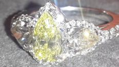 Exclusive handmade ring with a 1.04 ct fancy yellow diamond (with GIA report); pear cut diamonds on the sides, 0.60 each, colour:  G, clarity: VS2; accent diamonds 0.55 ct, clarity: VS, colour: E-F Total 2.79 ct