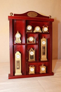 Ten gold-plated miniature clocks, with their display case - Second half of the 20th century