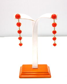 A pair of golden coral and diamond earrings.