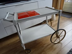 Vintage serving trolley made of wood with brass wheels