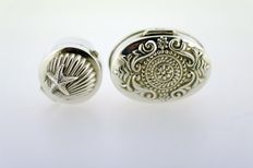 2 Silver pill boxes. One is Oval with ornaments, the other is round with a shell motif