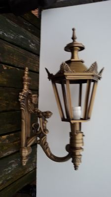 Large bronze outdoor wall light with a female figure.