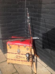 Old Vintage tackle box (equipment) filled with all kinds of fishing equipment with fishing rod, keepnet and landing net.