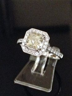 Entourage with cushion solitaire of  1.12 ct light greenish yellow, SI1.