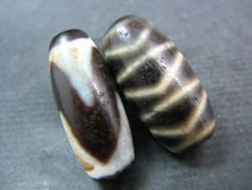 2 Dzi beads with tiger tooth and tiger stripe patterns - Himalayan regions - late 20th century.