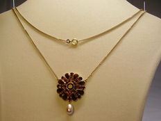 A gold necklace with garnet and a genuine pearl