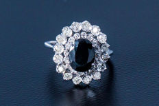A 750 white gold ring with a central sapphire of approx. 2.0 ct, flanked by 32 diamonds of approx. 1.12 ct