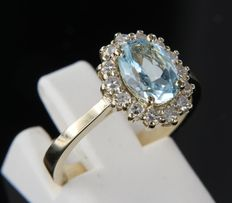 14 kt yellow gold entourage ring set with blue topaz and 14 pieces of octagon cut diamonds, ring size 16.5 (52)