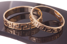 Set of gold partner rings with meander pattern