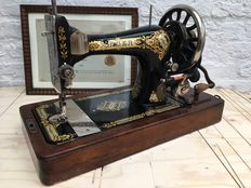 Floral decorated Singer sewing machine with framed certificate and housing, 1912