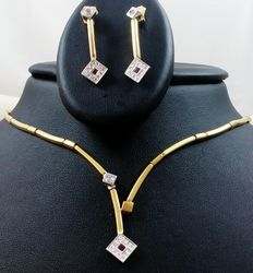 18 kt (750/1000) white and yellow gold choker with pendant and dangle earrings, with ruby gemstones and diamonds in square-shaped  bezel setting design. Total weight: 17.60 g.