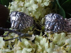 2 solid silver lion head's rings with continuing manes to the side of the rings