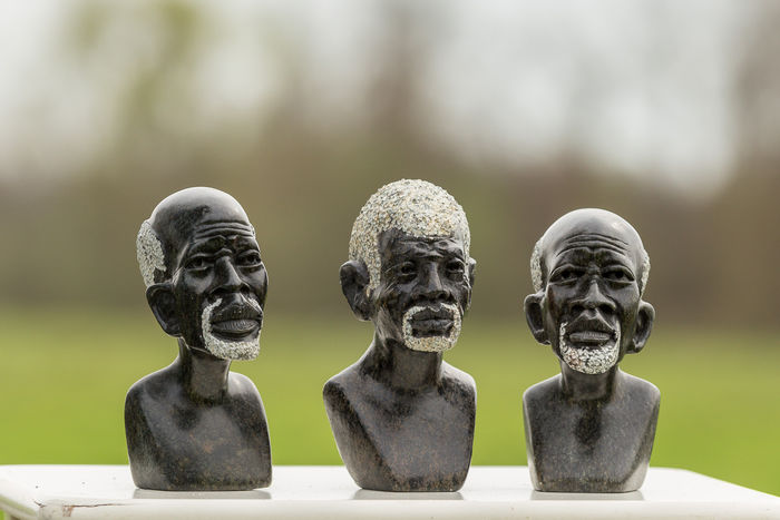 Three sculptures of African men
