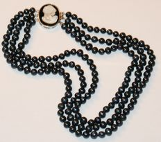 Black, freshwater pearl. Three-row necklace, mother of pearl clasp. Weight 101 g. Length 50 cm.