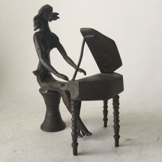 Unknown artist - bronze plated sculpture of a woman behind a small piano