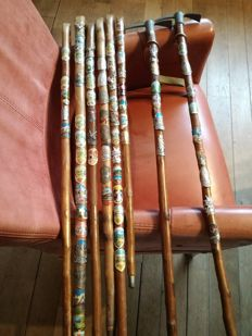 Collection of 8 walking sticks with souvenir pictures