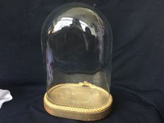 Old oval glass jar with wooden base