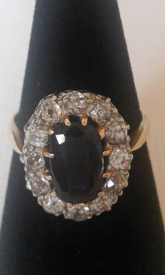 Daisy ring in yellow and grey gold with a central faceted oval sapphire and set with 12 diamonds