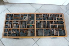 Old printer's tray drawer from a typecase cabinet of a printing company, with approximately 165 original block letters and numerals