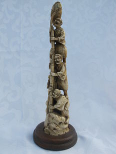 Ivory okimono with a wooden base, depicting four screaming men that are holding on to a lotus flower – Japan – Late 19th century