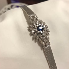 Semi-rigid 18 kt white gold bracelet with central setting featuring diamonds and composite oval cut sapphire.