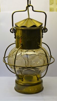 Brass ship's lamp equipped with smokey glass and an electric light fixture.