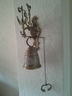 Large brass monastery bell with decorative elements.