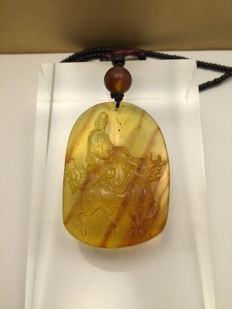 "Burmese Amber  engraved  pendant depicting a rider on a bull, theme: ""Guanyin"" weight: 20 grams"