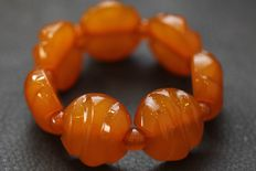 large bracelet of Baltic amber, carving, old butterscotch; Bracelet's width 31 mm, thickness 14 mm, length approx 290 mm