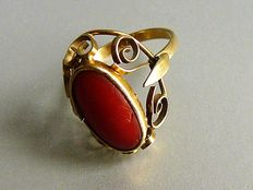 Gold ring with open worked edge and cabochon cut red corral