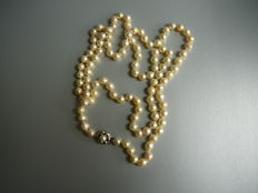 Long baroque necklace with a 14 kt white gold clasp with a pearl, 90 cm in length.