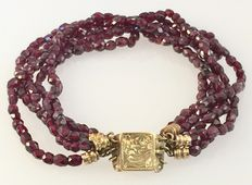 Bracelet with five strands of farmers garnet and yellow gold clasp.