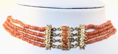 Red coral necklace with four strands and yellow gold clasp.