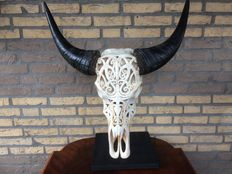 A carved buffalo skull on stand - approx1950, Spain
