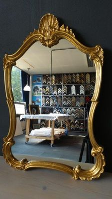 Venetian-style crest mirror with gilded frame.