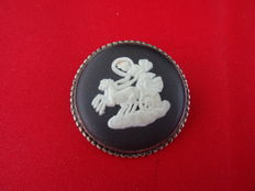 Silver English Wedgwood brooch with decoration of a carriage with horses and rider.