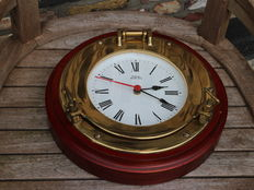 Royal mariner ship's clock in brass porthole on heavy wooden ring.