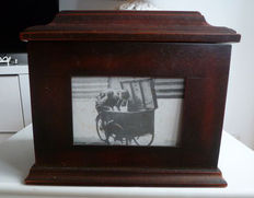 Heavy wooden box surrounded with photo frames, 20th century